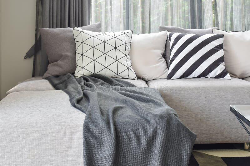Ο γκρίζος καναπές μορφής Λ με ποικίλλει το σχέδιο και τα άσπρα μαξιλάρια μέσα στοκ φωτογραφία