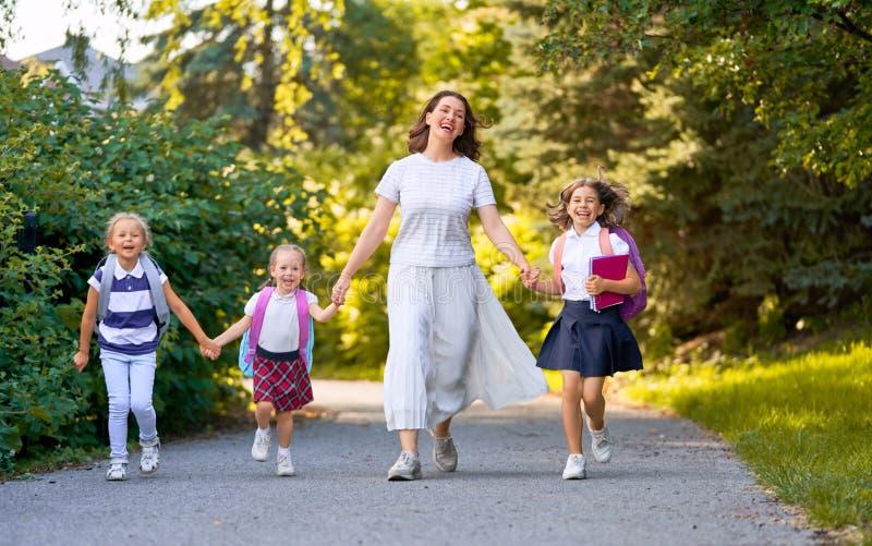 Ο γονέας και οι μαθητές πηγαίνουν στο σχολείο στοκ εικόνες