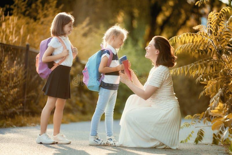 Ο γονέας και οι μαθητές πηγαίνουν στο σχολείο στοκ φωτογραφία