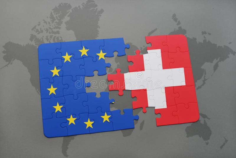 Ο γρίφος με τη εθνική σημαία της ευρωπαϊκής ένωσης της Ελβετίας και σε έναν κόσμο χαρτογραφεί το υπόβαθρο στοκ εικόνες
