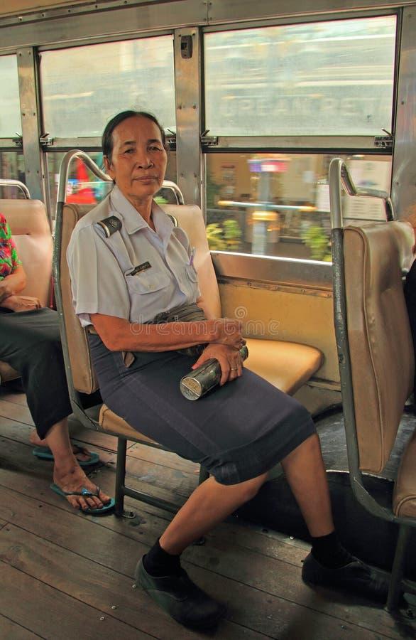 Ο γυναίκα-αγωγός στο λεωφορείο κάθεται σε ένα κάθισμα στοκ εικόνες