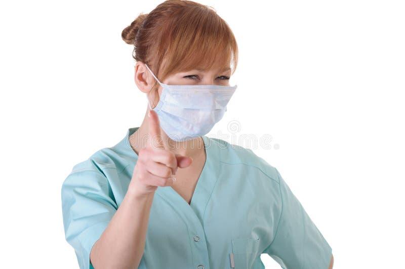 Ο γυναικείος γιατρός με την τοποθέτηση αναπνευστικών συσκευών και παρουσιάζει δάχτυλο σε σας στοκ φωτογραφία