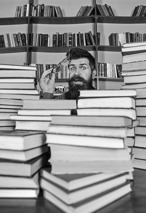 Ο δάσκαλος ή ο σπουδαστής με τη γενειάδα φορά eyeglasses, κάθεται στον πίνακα με τα βιβλία, έννοια επιστημονικής έρευνας Άτομο επ στοκ εικόνες με δικαίωμα ελεύθερης χρήσης