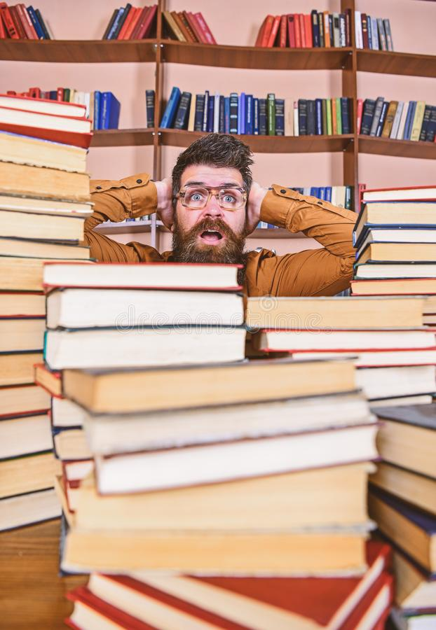 Ο δάσκαλος ή ο σπουδαστής με τη γενειάδα φορά eyeglasses, κάθεται στον πίνακα με τα βιβλία, Άτομο στο συγκλονισμένο πρόσωπο μεταξ στοκ φωτογραφία με δικαίωμα ελεύθερης χρήσης