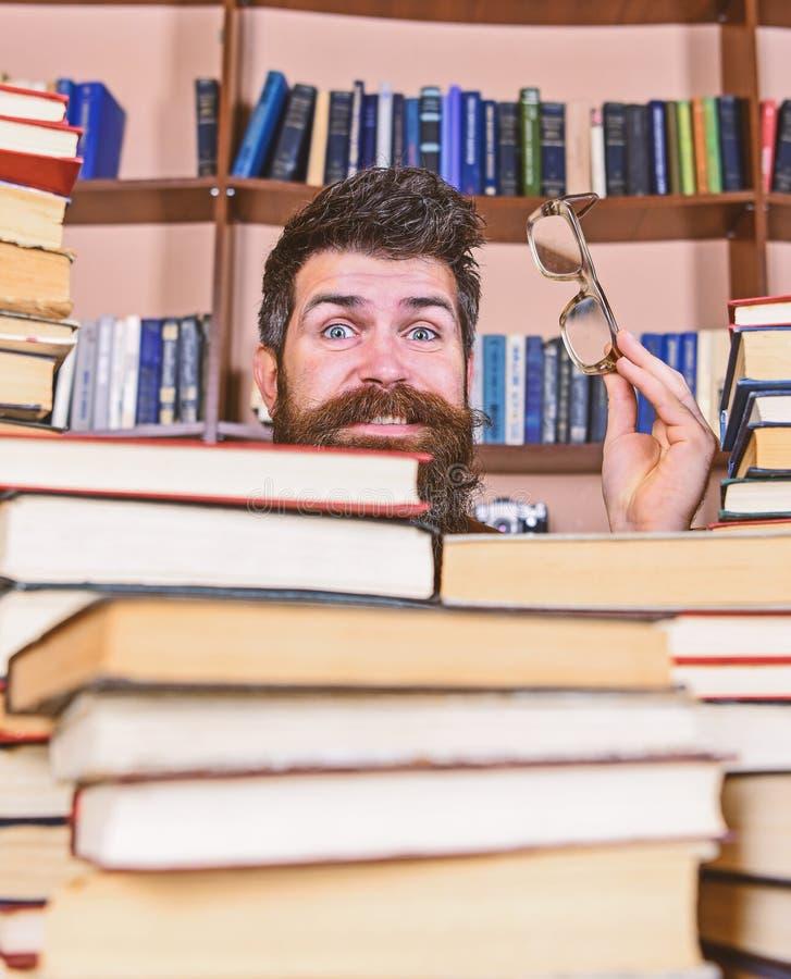 Ο δάσκαλος ή ο σπουδαστής με τη γενειάδα φορά eyeglasses, κάθεται στον πίνακα με τα βιβλία, Άτομο στο έκπληκτο πρόσωπο μεταξύ των στοκ φωτογραφία
