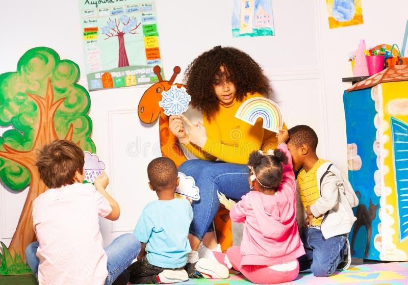 Ο δάσκαλος στο παιδικό σταθμό παρουσιάζει καιρικές κάρτες στοκ φωτογραφία