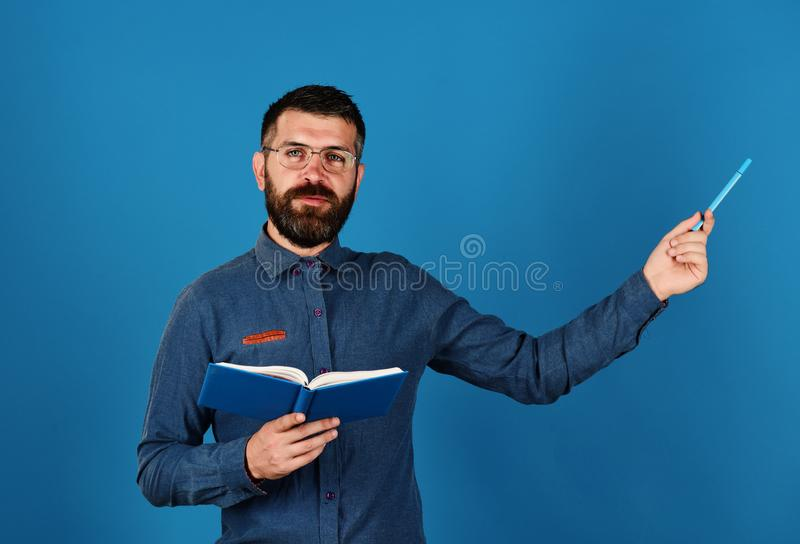 Ο δάσκαλος φορά τα γυαλιά και κρατά το διοργανωτή και τη μάνδρα Άτομο με τη γενειάδα και το βιβλίο Έννοια γνώσης και μαθήματος στοκ εικόνες