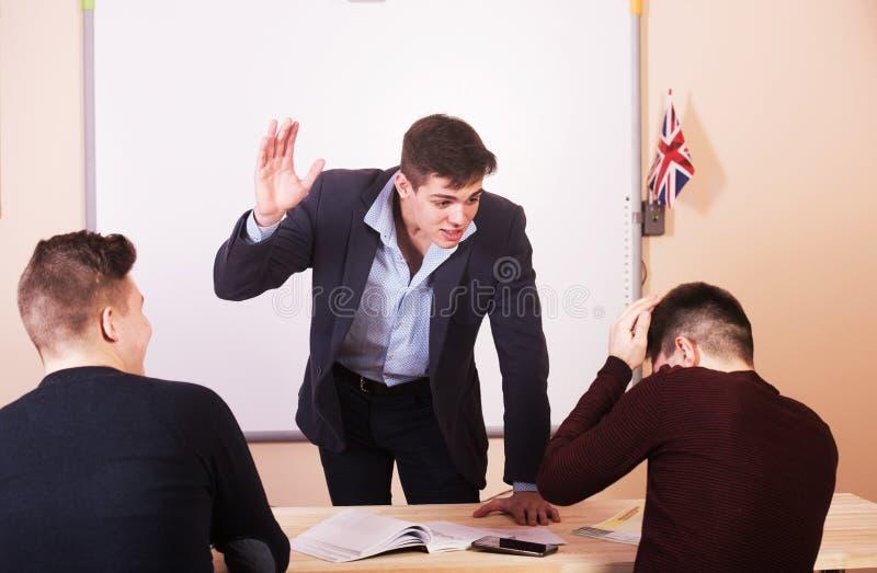 Ο δάσκαλος Youn απειλεί τον αποσπασμένο σπουδαστή κατά τη διάρκεια του μαθήματος στοκ φωτογραφία