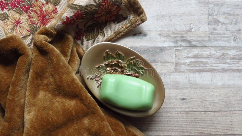 Ο δίσκος σαπουνιών αυξήθηκε διακοσμημένο, πράσινο σαπούνι, πετσέτα χρώματος πιπεροριζών Περιουσίες λουτρών στοκ φωτογραφίες με δικαίωμα ελεύθερης χρήσης