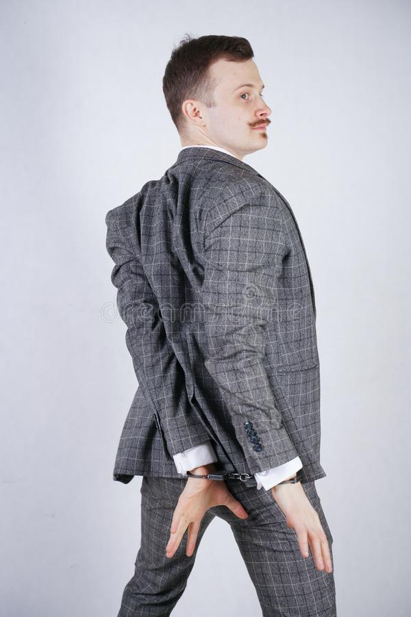 Ο δαπανηρά ντυμένος κλέφτης πάσχει από την κλεπτομανία και συλλαμβάνεται για ένα έγκλημα ένα άτομο στάσεις επιχειρησιακών στις μο στοκ εικόνα