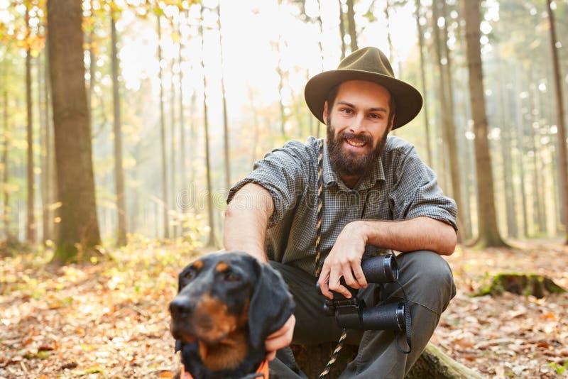 Ο δασοφύλακας με το κυνήγι του σκυλιού και των διοπτρών παίρνει ένα σπάσιμο στοκ φωτογραφίες