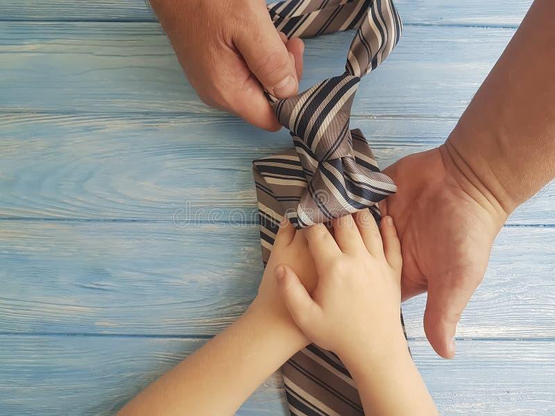Ο δεσμός μπαμπάδων και παιδιών χεριών ημέρας πατέρων ` s ευχαριστεί στο μπλε ξύλινο κλίμα στοκ εικόνες