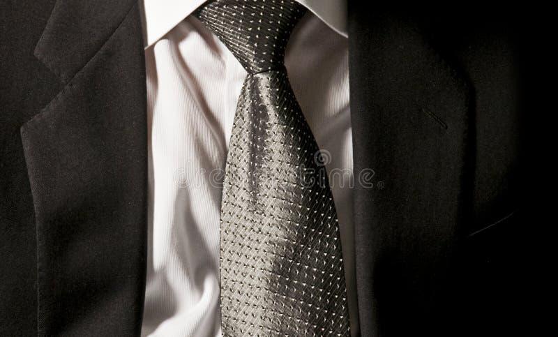 Ο δεσμός του προϊσταμένου Ο επιχειρηματίας φορά το σκοτεινό γκρίζο σακάκι του στο άσπρο πουκάμισο με έναν κομψό γκρίζο δεσμό στοκ εικόνα