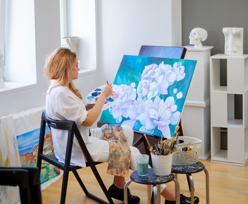 Ο δημιουργικός ζωγράφος χρωματίζει μια ζωηρόχρωμη εικόνα στο στούντιό της στοκ φωτογραφία με δικαίωμα ελεύθερης χρήσης