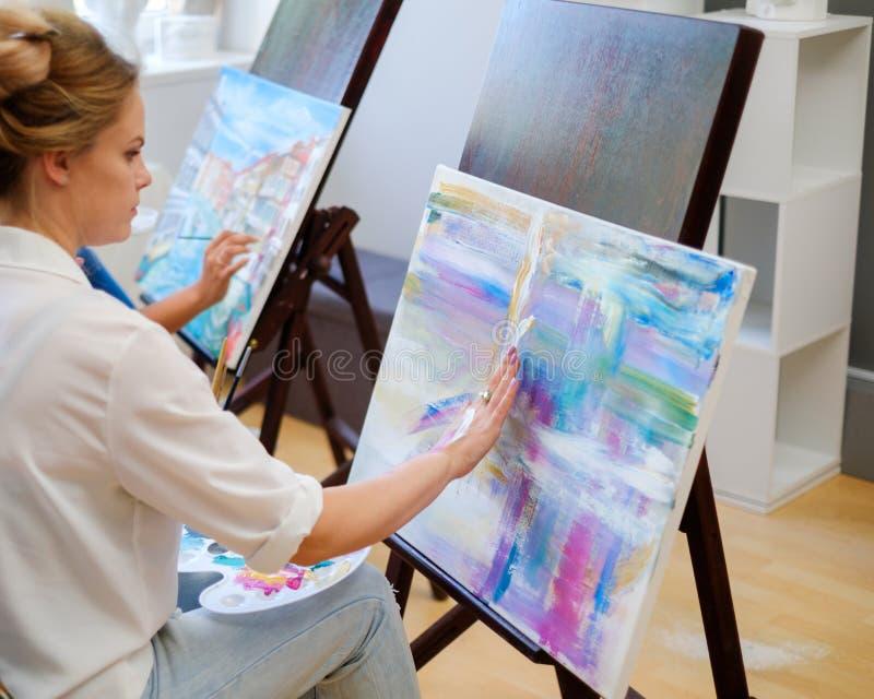 Ο δημιουργικός ζωγράφος χρωματίζει μια ζωηρόχρωμη εικόνα στο στούντιό της στοκ εικόνα