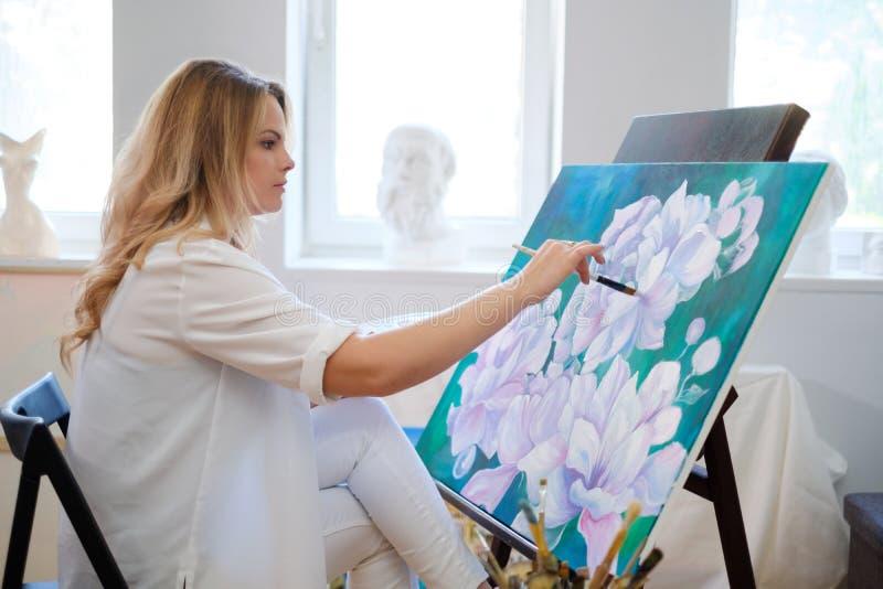 Ο δημιουργικός ζωγράφος χρωματίζει μια ζωηρόχρωμη εικόνα στο στούντιό της στοκ εικόνες