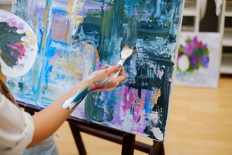 Ο δημιουργικός ζωγράφος χρωματίζει μια ζωηρόχρωμη εικόνα στο στούντιό της στοκ φωτογραφία