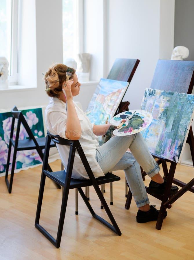 Ο δημιουργικός ζωγράφος χρωματίζει μια ζωηρόχρωμη εικόνα στο στούντιό της στοκ φωτογραφίες