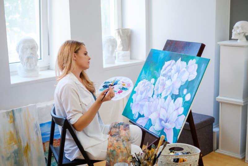 Ο δημιουργικός ζωγράφος χρωματίζει μια ζωηρόχρωμη εικόνα στο στούντιό της στοκ εικόνες με δικαίωμα ελεύθερης χρήσης