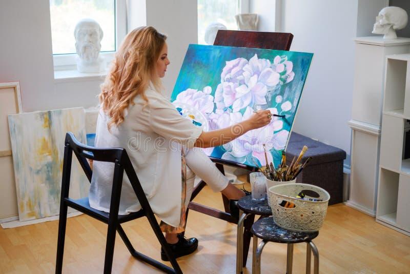 Ο δημιουργικός ζωγράφος χρωματίζει μια ζωηρόχρωμη εικόνα στο στούντιό της στοκ φωτογραφίες με δικαίωμα ελεύθερης χρήσης