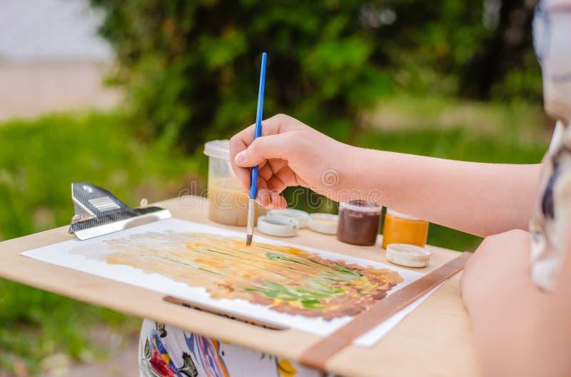 Ο δημιουργικός καλλιτέχνης χρωματίζει μια ζωηρόχρωμη εικόνα Κινηματογράφηση σε πρώτο πλάνο των χεριών και της βούρτσας στο στάδιο στοκ εικόνα με δικαίωμα ελεύθερης χρήσης