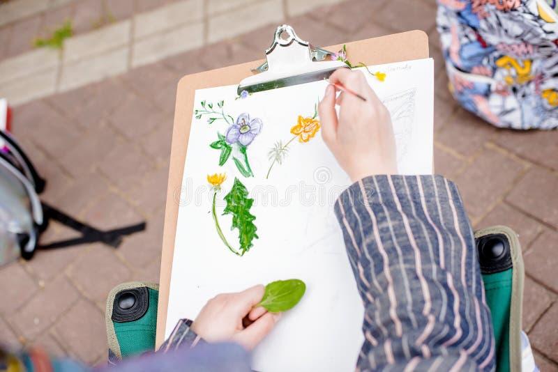 Ο δημιουργικός καλλιτέχνης χρωματίζει μια ζωηρόχρωμη εικόνα Κινηματογράφηση σε πρώτο πλάνο των χεριών και της βούρτσας στο στάδιο στοκ εικόνα