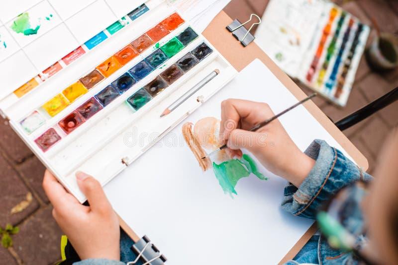 Ο δημιουργικός καλλιτέχνης χρωματίζει μια ζωηρόχρωμη εικόνα Κινηματογράφηση σε πρώτο πλάνο των χεριών και της βούρτσας στο στάδιο στοκ φωτογραφία