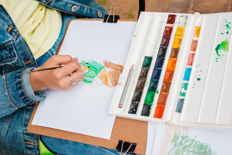 Ο δημιουργικός καλλιτέχνης χρωματίζει μια ζωηρόχρωμη εικόνα Κινηματογράφηση σε πρώτο πλάνο των χεριών και της βούρτσας στο στάδιο στοκ εικόνες