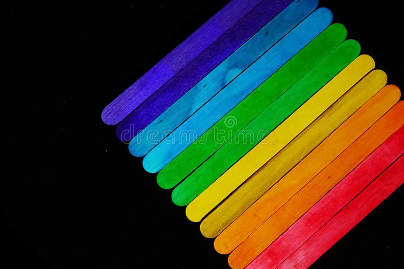 Ο διαγώνιος χρωματισμένος ξύλινος φραγμός που τοποθετούν διαδοχικά στον τόνο φάσματος στο μαύρο υπόβαθρο και το διάστημα για γράφ στοκ φωτογραφία