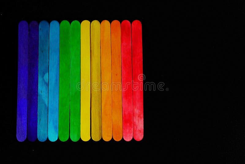 Ο διαγώνιος χρωματισμένος ξύλινος φραγμός που τοποθετούν διαδοχικά στον τόνο φάσματος στο μαύρο υπόβαθρο και το διάστημα για γράφ στοκ φωτογραφίες