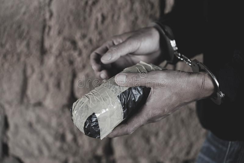 Ο διακινητής ναρκωτικών κάτω από τη σύλληψη περιόρισε με τις χειροπέδες μαζί με την ηρωίνη, το νόμο και την έννοια αστυνομίας Παγ στοκ φωτογραφίες