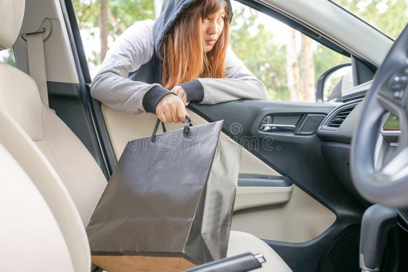 Ο διαρρήκτης γυναικών κλέβει μια τσάντα αγορών μέσω του παραθύρου του αυτοκινήτου - τ στοκ εικόνα