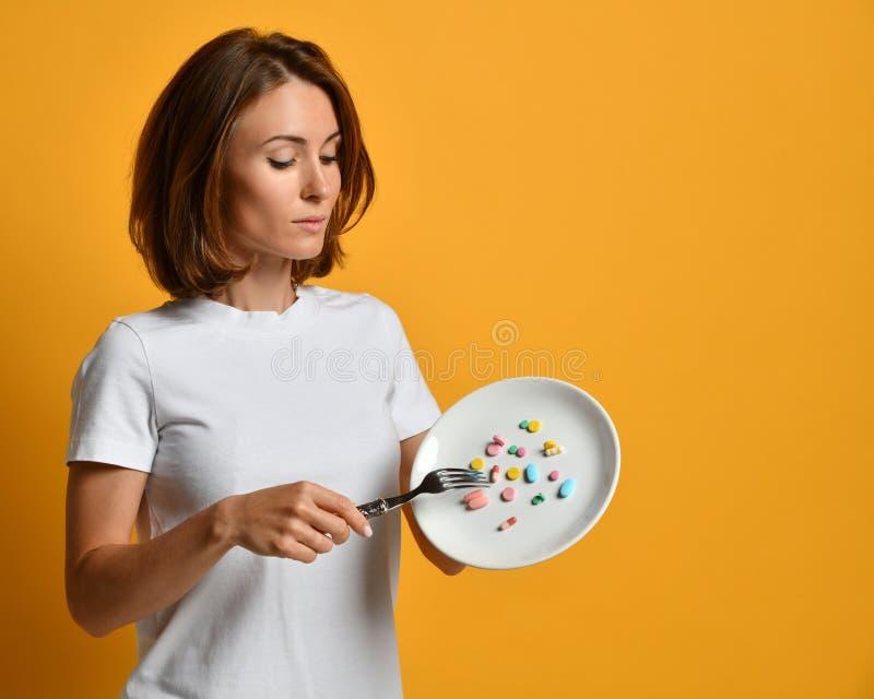 Ο διατροφολόγος γυναικών κρατά ένα άσπρο πιάτο με τα διαφορετικά φάρμακα απώλειας βάρους συνταγών συμπληρωμάτων διατροφής χαπιών  στοκ εικόνα με δικαίωμα ελεύθερης χρήσης