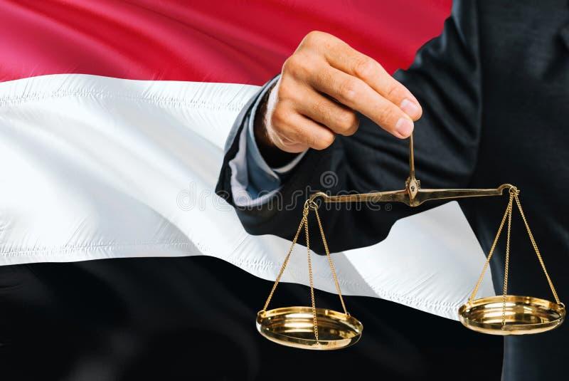 Ο δικαστής Γιεμενιτών κρατά τις χρυσές κλίμακες της δικαιοσύνης με το κυματίζοντας υπόβαθρο σημαιών της Υεμένης Θέμα ισότητας και στοκ φωτογραφίες με δικαίωμα ελεύθερης χρήσης