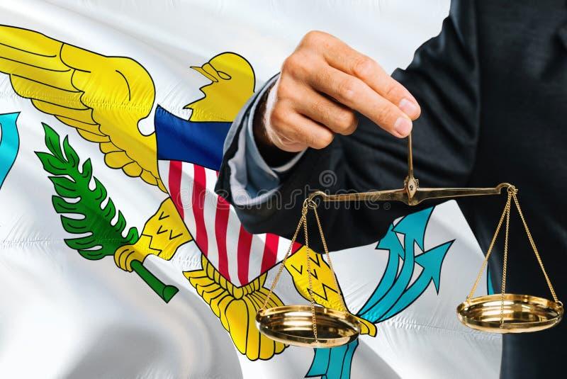 Ο δικαστής κρατά τις χρυσές κλίμακες δικαιοσύνη με τους Ηνωμένους Παρθένους Νήσους που κυματίζουν το υπόβαθρο σημαιών Θέμα ισότητ στοκ εικόνα