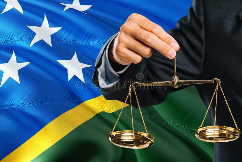 Ο δικαστής κρατά τις χρυσές κλίμακες της δικαιοσύνης με τις νήσους του Σολομώντος που κυματίζουν το υπόβαθρο σημαιών Θέμα ισότητα στοκ φωτογραφίες με δικαίωμα ελεύθερης χρήσης