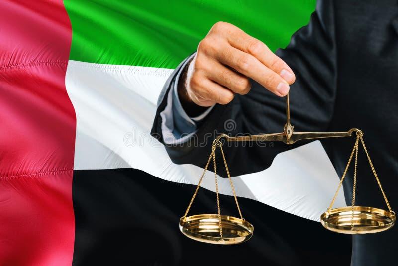 Ο δικαστής κρατά τις χρυσές κλίμακες της δικαιοσύνης με τα Ηνωμένα Αραβικά Εμιράτα που κυματίζουν το υπόβαθρο σημαιών Θέμα ισότητ στοκ φωτογραφίες
