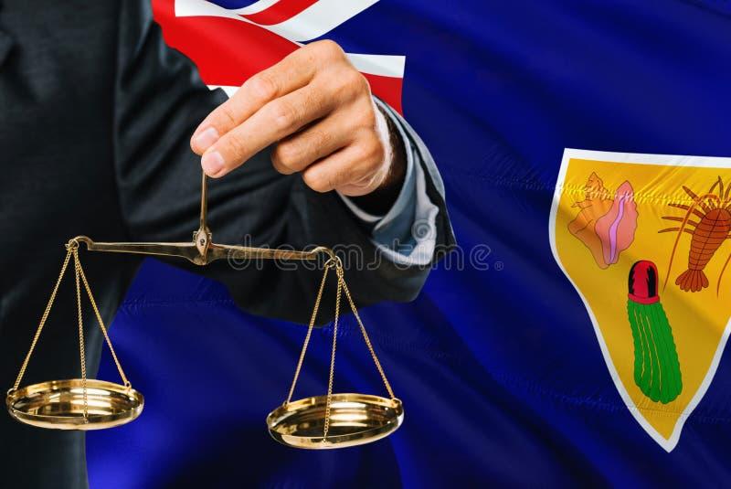 Ο δικαστής κρατά τις χρυσές κλίμακες της δικαιοσύνης με τους Νήσους Τερκς και Κάικος κυματίζοντας το υπόβαθρο σημαιών Θέμα ισότητ στοκ εικόνες