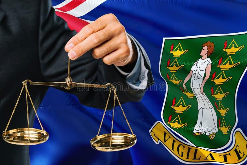 Ο δικαστής κρατά τις χρυσές κλίμακες της δικαιοσύνης με τους βρετανικούς Παρθένους Νήσους που κυματίζουν το υπόβαθρο σημαιών Θέμα στοκ εικόνες