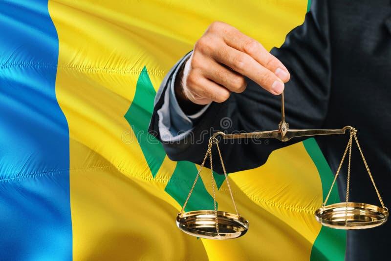 Ο δικαστής κρατά τις χρυσές κλίμακες της δικαιοσύνης με το Άγιο Βικέντιο και Γρεναδίνες που κυματίζει το υπόβαθρο σημαιών Θέμα ισ στοκ φωτογραφία
