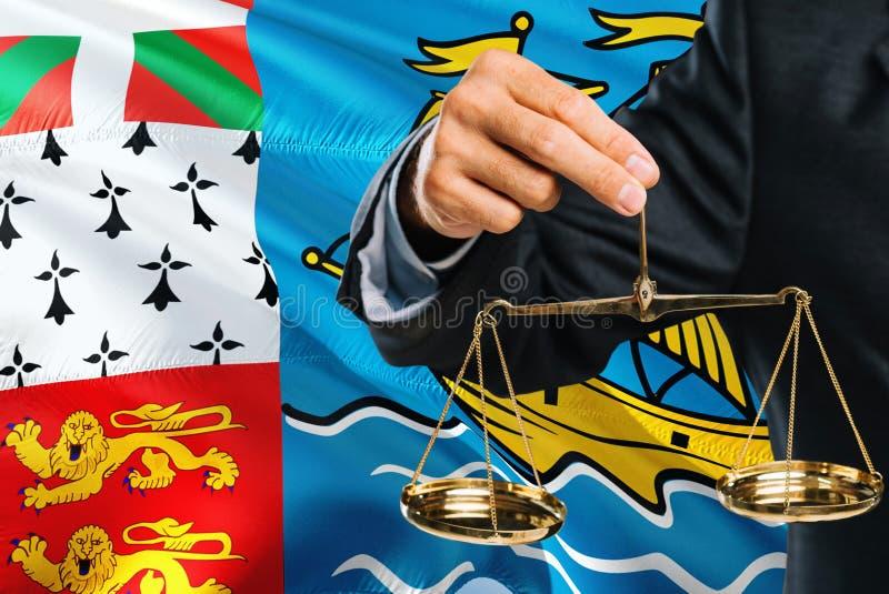 Ο δικαστής κρατά τις χρυσές κλίμακες της δικαιοσύνης με το Σαιν Πιέρ και Μικελόν που κυματίζει το υπόβαθρο σημαιών Θέμα ισότητας  στοκ φωτογραφία με δικαίωμα ελεύθερης χρήσης