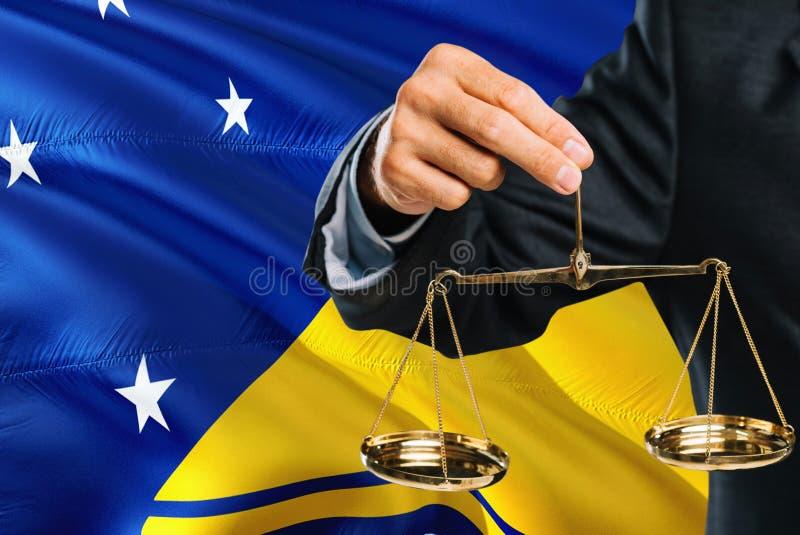 Ο δικαστής κρατά τις χρυσές κλίμακες της δικαιοσύνης με το Τοκελάου που κυματίζει το υπόβαθρο σημαιών Θέμα ισότητας και νομική έν στοκ εικόνες