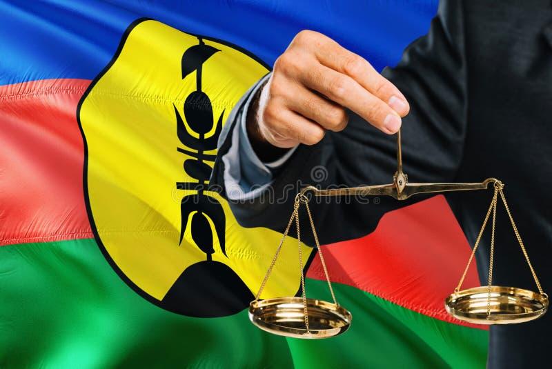 Ο δικαστής κρατά τις χρυσές κλίμακες της δικαιοσύνης με το κυματίζοντας υπόβαθρο σημαιών της Νέας Καληδονίας Θέμα ισότητας και νο ελεύθερη απεικόνιση δικαιώματος