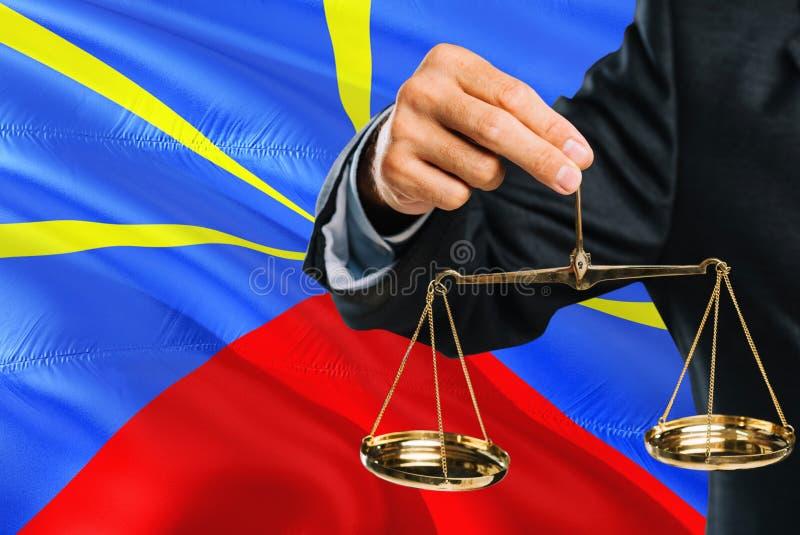 Ο δικαστής κρατά τις χρυσές κλίμακες της δικαιοσύνης με το κυματίζοντας υπόβαθρο σημαιών συγκέντρωσης Θέμα ισότητας και νομική έν στοκ φωτογραφίες
