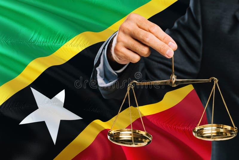 Ο δικαστής κρατά τις χρυσές κλίμακες της δικαιοσύνης με το κυματίζοντας υπόβαθρο σημαιών Σαιντ Κιτς και Νέβις Θέμα ισότητας και ν στοκ εικόνα με δικαίωμα ελεύθερης χρήσης