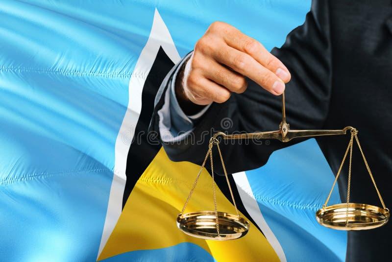 Ο δικαστής κρατά τις χρυσές κλίμακες της δικαιοσύνης με το κυματίζοντας υπόβαθρο σημαιών Αγιών Λουκία Θέμα ισότητας και νομική έν στοκ φωτογραφία με δικαίωμα ελεύθερης χρήσης
