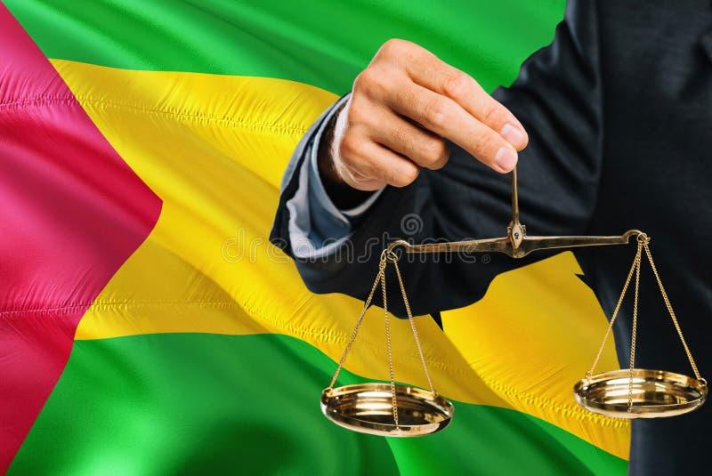 Ο δικαστής κρατά τις χρυσές κλίμακες της δικαιοσύνης με το κυματίζοντας υπόβαθρο σημαιών του Σάο Τομέ και Πρίντσιπε Θέμα ισότητας στοκ φωτογραφία