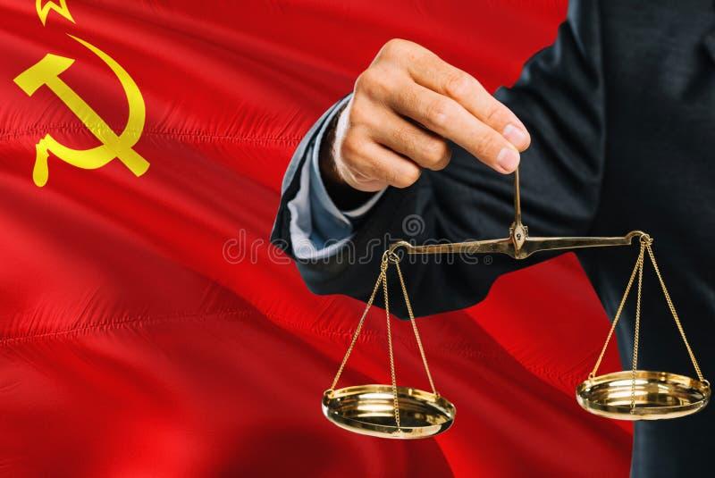 Ο δικαστής κρατά τις χρυσές κλίμακες της δικαιοσύνης με το κυματίζοντας υπόβαθρο σημαιών της Σοβιετικής Ένωσης Θέμα ισότητας και  στοκ φωτογραφίες με δικαίωμα ελεύθερης χρήσης