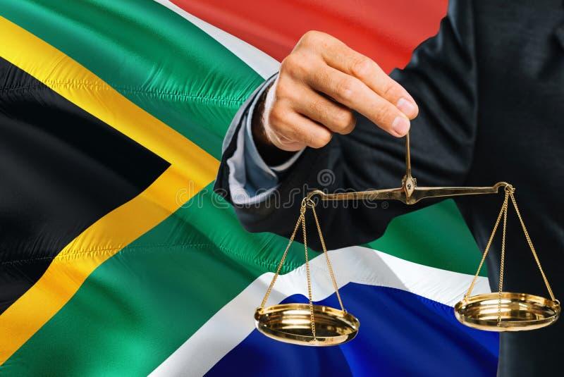 Ο δικαστής κρατά τις χρυσές κλίμακες της δικαιοσύνης με το κυματίζοντας υπόβαθρο σημαιών της Νότιας Αφρικής Θέμα ισότητας και νομ στοκ εικόνες