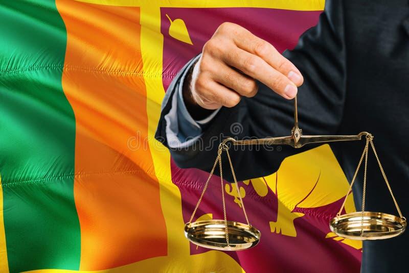 Ο δικαστής κρατά τις χρυσές κλίμακες της δικαιοσύνης με το κυματίζοντας υπόβαθρο σημαιών της Σρι Λάνκα Θέμα ισότητας και νομική έ στοκ φωτογραφία